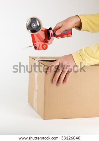 Person closing a cardboard box with packing tape. - stock photo