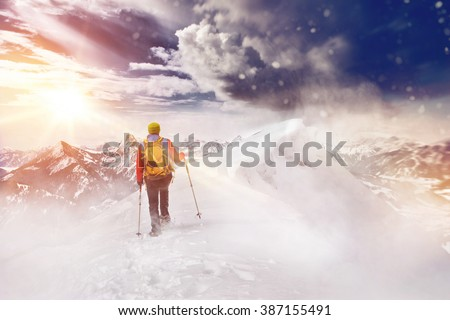 Person cross country skiing or Nordic walking or hiking in a beautiful snow covered mountain landscape facing towards the glow of the rising sun and rugged alpine peaks - stock photo