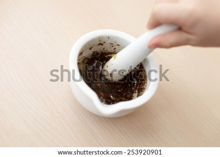 Person crushes spices in a mortar on the table - stock photo