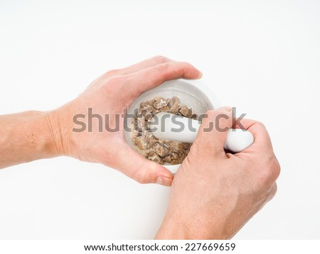 Person crushing brown sugar cubes in a white marble mortar - stock photo
