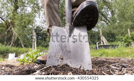 Person digging bare earth on a plot of land with a close up view of the spade. - stock photo