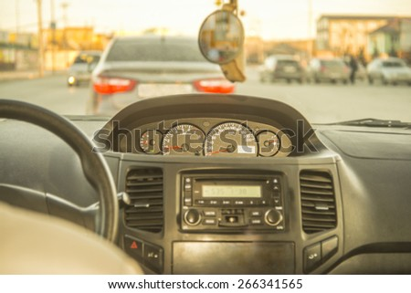 Person driving a car at sunset evening sky light Autumn Road between houses control Focus on arrow speedometer and tachometer audio system Empty copy space for inscription - stock photo