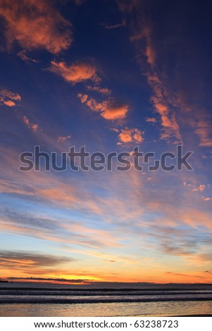 Person enjoys beautiful Sunset from the beach - stock photo