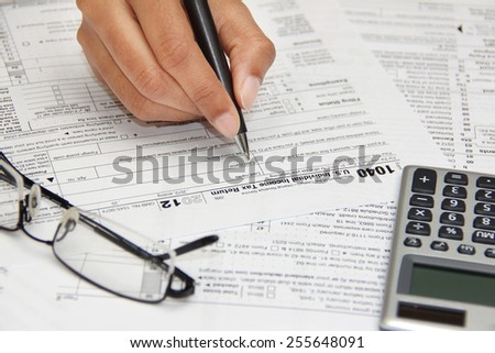 Person filling 1040 federal tax form - stock photo