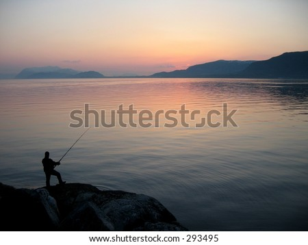 Person fishing at sea shore. - stock photo