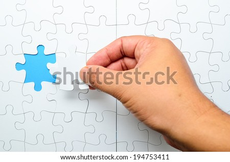Person fitting the last puzzle piece.Concept image of building and button up