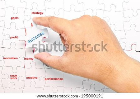 Person fitting the last puzzle piece.Concept image of SUCCESS - stock photo