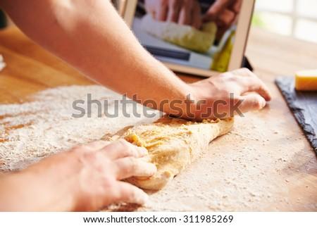 Person Following Pizza Recipe Using App On Digital Tablet - stock photo