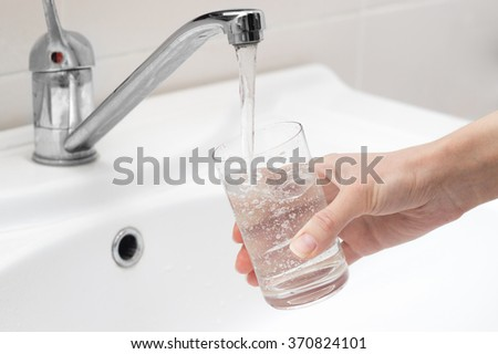 person gaining cold drinking water from the tap - stock photo