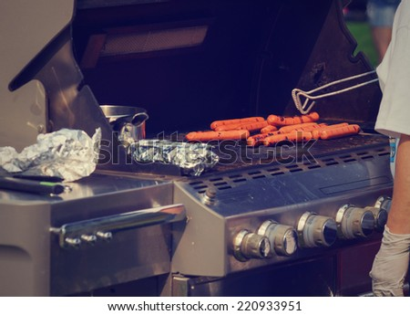 person grilling hot dogs in park with instagram filter - stock photo