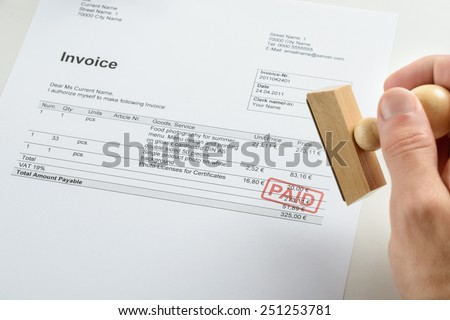 Person Hand Holding Rubber Stamp Over Red Paid Stamp On Invoice - stock photo