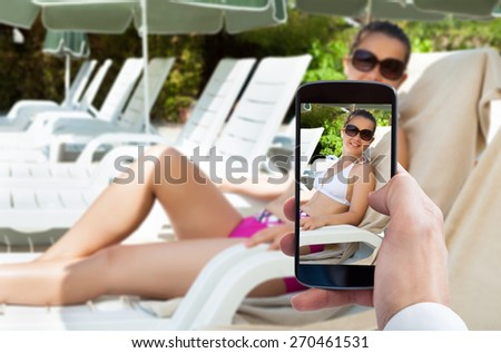 Person Hand Photographing Woman Sitting On Lounge Chair - stock photo