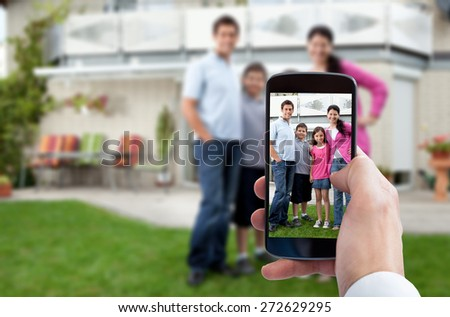 Person Hand Using Mobile Phone For Taking Family Photo - stock photo