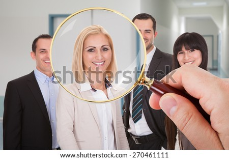 Person Hand With Magnifying Glass Looking At Candidate - stock photo