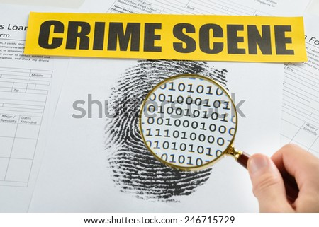 Person Hand With Magnifying Glass Over Document Revealing Binary Code And Crime Scene Tape On It - stock photo