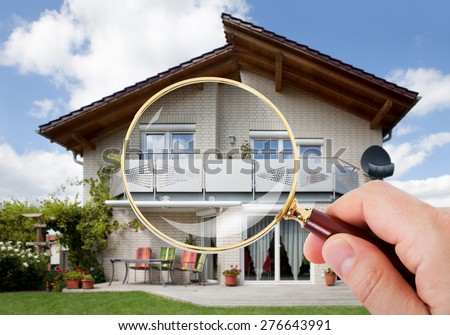 Person Hand With Magnifying Glass Over Luxury House - stock photo