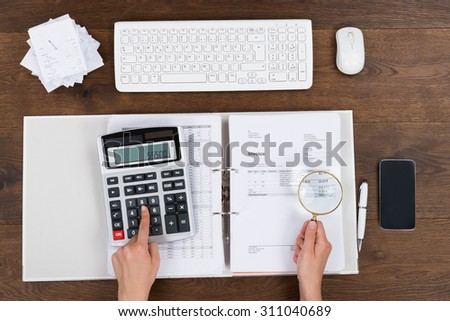 Person Hands Checking Invoice With Magnifying Glass At Wooden Desk - stock photo