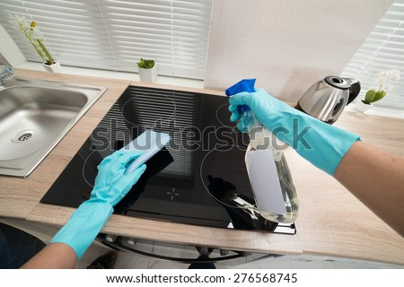 Person Hands In Blue Glove Cleaning Induction Stove - stock photo