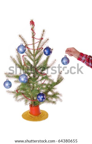 Person hangs the last ornament on their little christmas tree on white