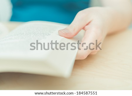 Person holding a book in shallow focus - stock photo