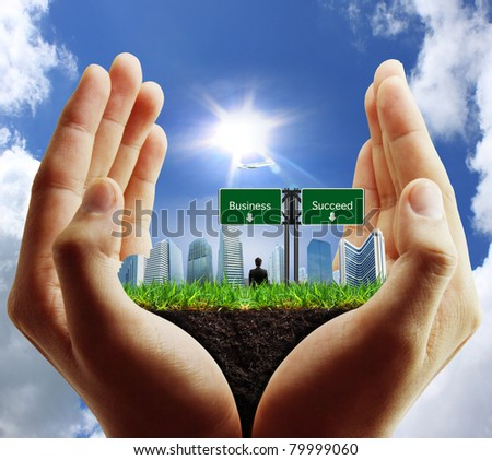 person holding a business, building on hand - stock photo