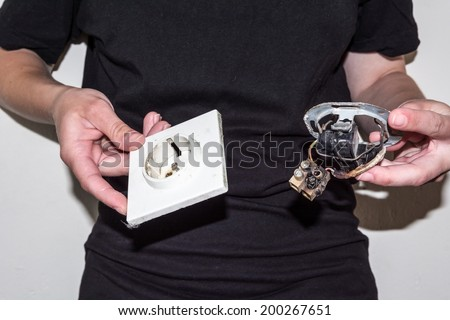 Person holding a damaged electric socket in her hands