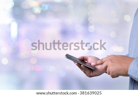 person holding a smartphone on blurred cityscape background - stock photo