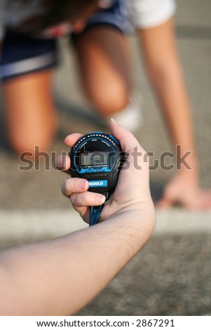 person holding a stop watch in front of a runner ready to start a race - stock photo