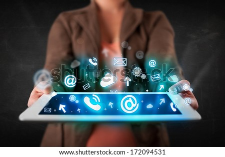 Person holding a white tablet with blue technology icons and symbols - stock photo