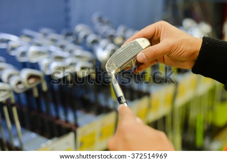 Person holding in hand club at a golf shop. Closeup photo of choice concept - stock photo