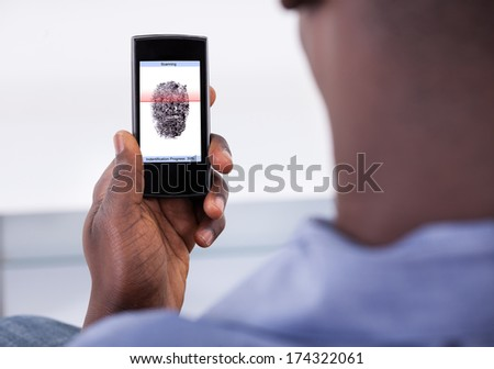 Person Holding Mobile Phone Showing Application With Process Of Scanning Fingerprint On A Screen - stock photo