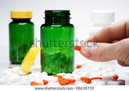 person holding one pill with a variety of pills on table and medicine bottles in background - stock photo