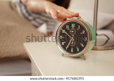Person in bed reaching out to switch off an alarm clock set for seven in the morning as a wake up call - stock photo