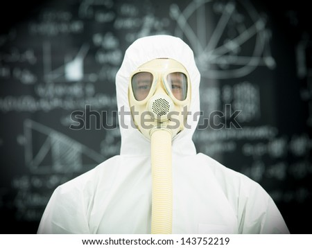 person in protective gear with gas mask in front of a blackboard  with graphics and formulas written on it in chalk - stock photo