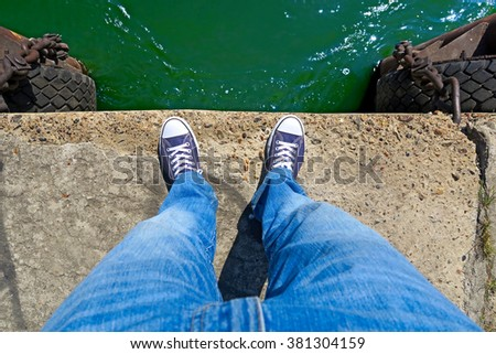 Person in the Jeans and Sneakers on the Edge - stock photo