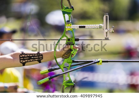 Person is shooting with recurve bow during an archery competition. Hand and bow only. Green bow. - stock photo