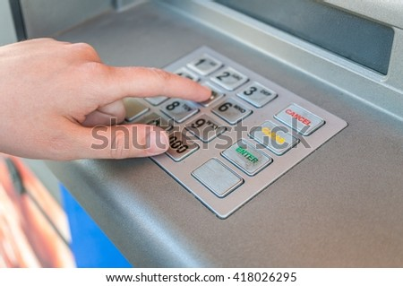 Person is using keypad and entering pin code in ATM machine. Banking concept. - stock photo