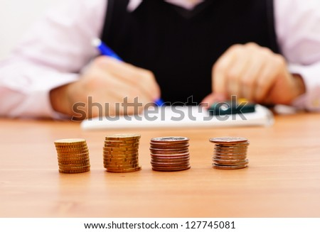 Person is writing and counting money on a wooden table