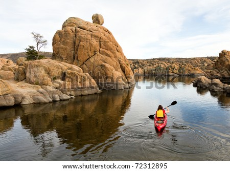 Person Kayaking on Calm Lake Surrounded by Boulders - stock photo