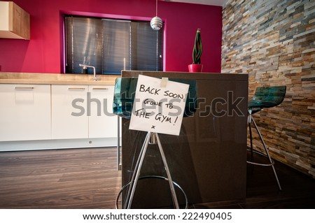 Person leaves note on kitchen stool saying Back Soon. Gone to The Gym! - stock photo