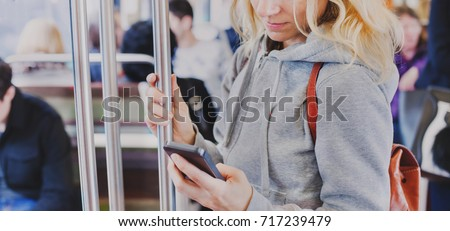 person looking at the screen of smart phone in subway, woman holding mobile in metro
