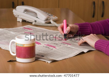 Person looking for work in the newspaper. Person is holding a bright pink highlighter pen and circling interesting jobs whilst drinking a cup of coffee. - stock photo