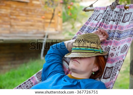 Person lying in Hammock at Patio of Wooden Rural Cottage relaxed and serene green Garden on background - stock photo