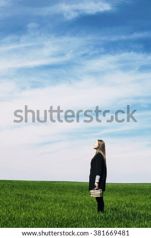 Person lying outdoors and reading a book. Cute young woman sitting on the grass and reading the book. A young woman lying on the grass and reading a book, lovely young girl reading a book - stock photo