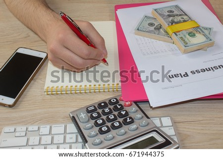 person Man pointing writing goals on a paper,writing business plan at workplace, man holding pens, papers, notes in documents, Saving money concept