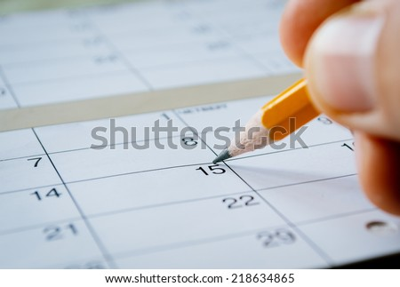 Person marking the date of the 15th with a pencil on a blank calendar with date squares as a reminder of an important day or to schedule a meeting or event - stock photo