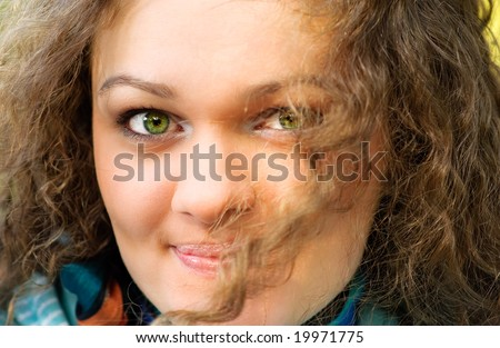 Person of girl with curly hair and green eyes.