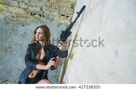 person of young sexy woman in a leather jacket and sexual brassiere with a Kalashnikov in her hand. Girl stand against brutal brick wall - stock photo