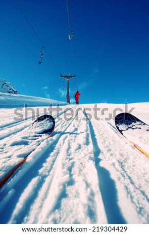 Person on a ski lift in the mountains - stock photo