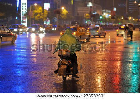 Person on bike covered with green poncho. Rainy night. Shanghai China - stock photo